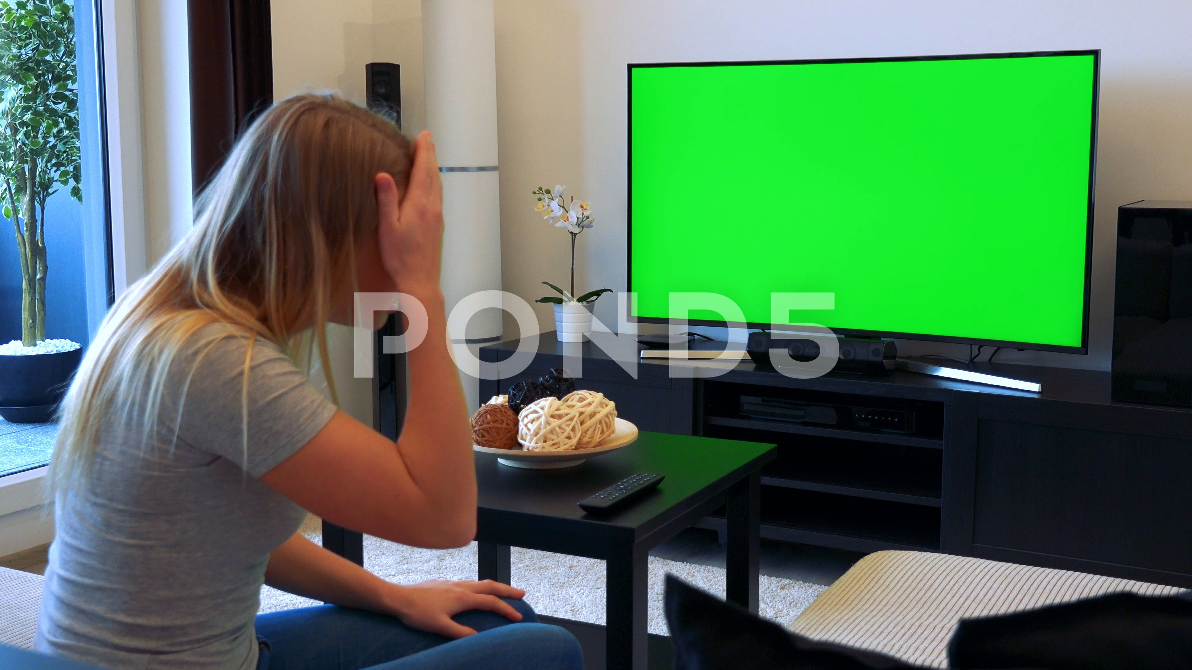 A Blonde Woman Sits On A Couch In A Living Room Watches Tv With A Green Screen Stock Footage Ad Couch Living Blonde Room Blonde Women Greenscreen Blonde