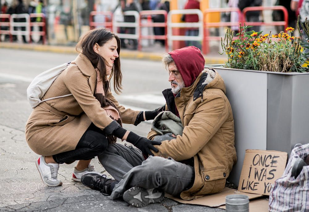 Young Woman Giving Money To Homeless Beggar Man Sitting In City
