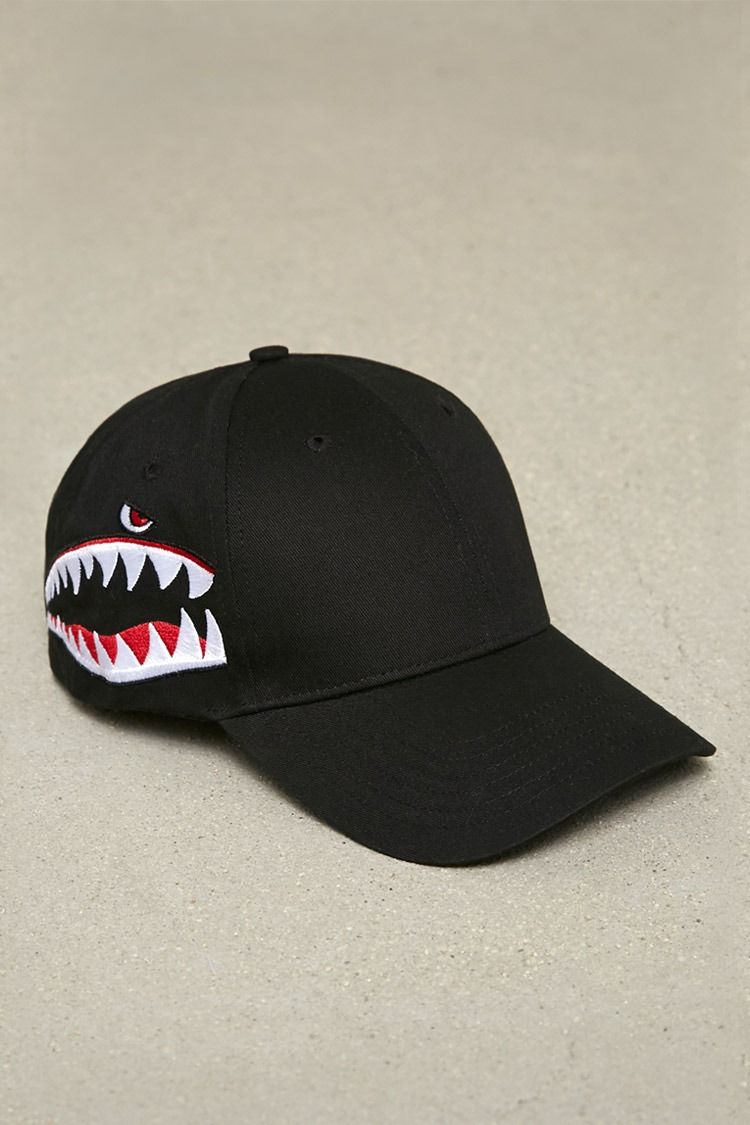 4e178258975 A canvas cap featuring shark mouth embroidery on the sides and an  adjustable back.