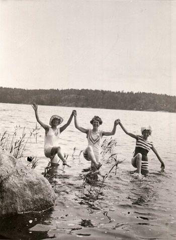 Tre kvinnor i baddräkt håller hand och dansar i vattnet. Uppland ... d92da8820fa84