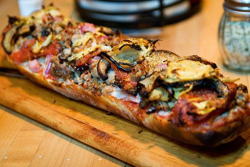 Fatty French bread pizza  topped with pepperoni, ham, pulled pork, sausage, mushroom, and eggplant. #BrooklynBowl / #FoodbyBlueRibbon / #FrenchBreadPizza