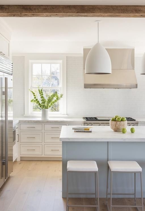 Exquisite white and gray kitchen is equipped with  stainless steel vent hood mounted against also