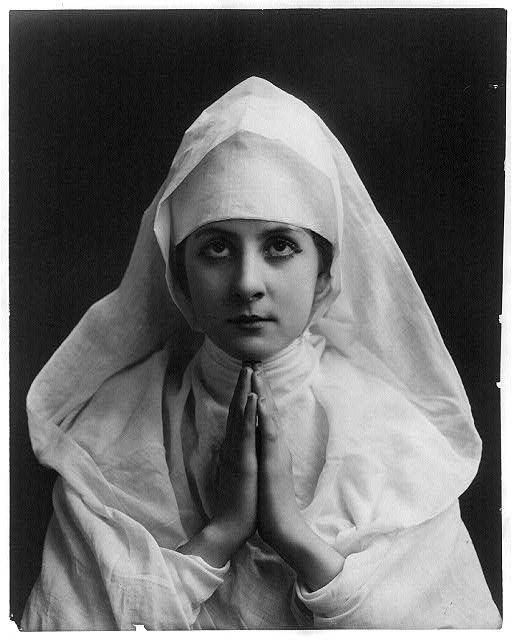 Young woman modeling: Half lgth., wearing nun's white habit and praying