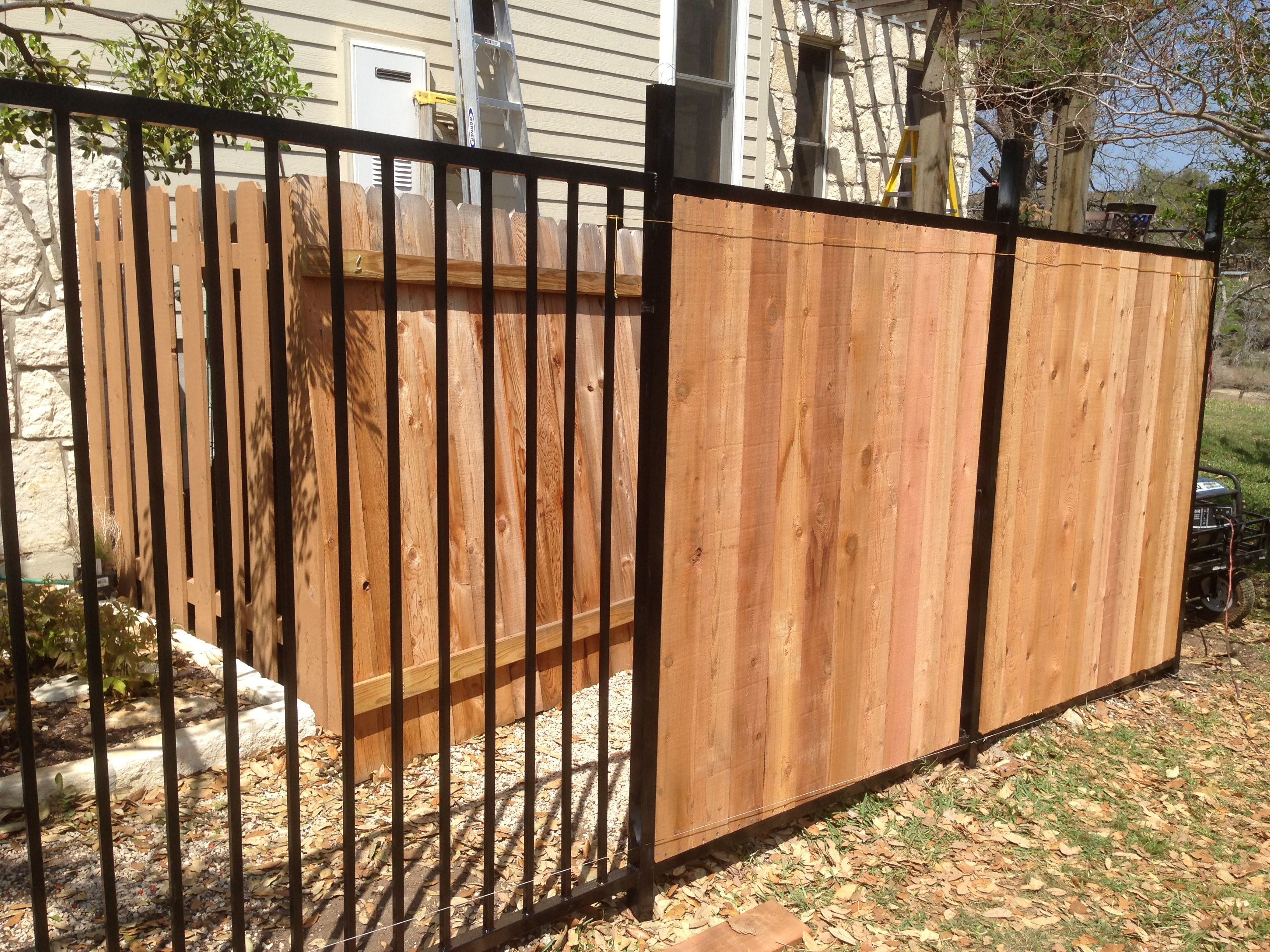 Custom wrought iron fence transitioning into privacy cedar fence