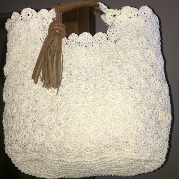 NWT's Ivory crochet style summer bag. NWT's Ivory crochet style summer bag with faux leather tassel and handle. Bags