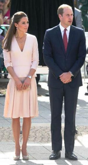 Kate Middleton in a soft pink Alexander McQueen top with v-neck and peplum detailing and a pleated A-line skirt.jpg