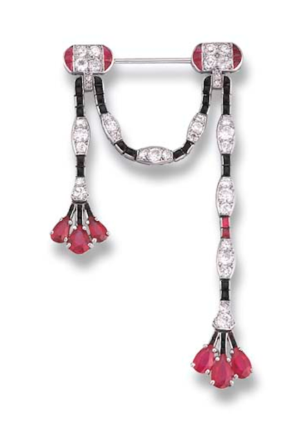 AN ATTRACTIVE ART DECO RUBY, DIAMOND AND ONYX BROOCH, BY CARTIER The diamond and onyx festoon with three-stone pear-shaped ruby tassels to the ruby and diamond clasp terminals, circa 1925, 4.0 cm. wide, with French assay marks for platinum Signed Cartier, Nos. 782, 845