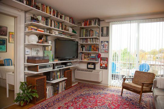 Phillip's Boldly Colorful Denver Apartment — House Call | LOVE the parisian rug and the versatile wall shelves