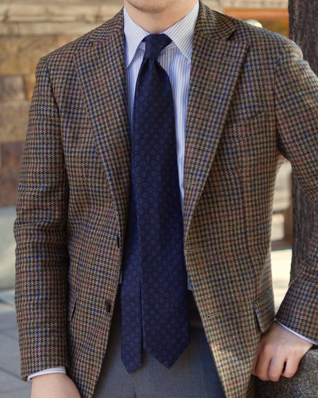 Brown herringbone tweed sport coat, white shirt with blue