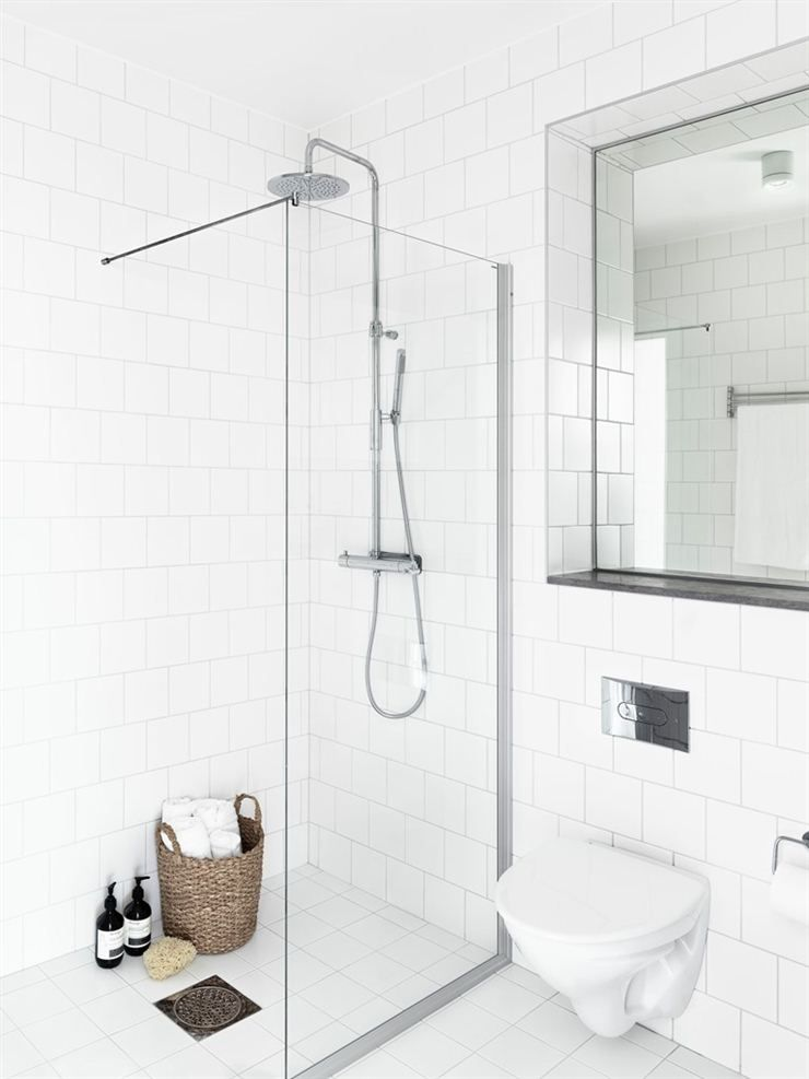 Shower open to front with glass panel dividing shower and toilet. Recessed mirror alcove over toilet.