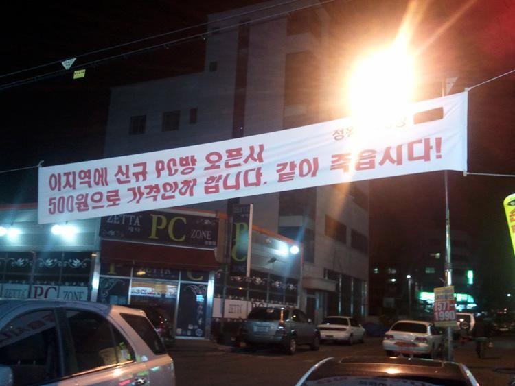 현수막 글귀: 이 지역에 신규 PC방 오픈시 500원으로 가격인하 합니다. 같이 죽읍시다!