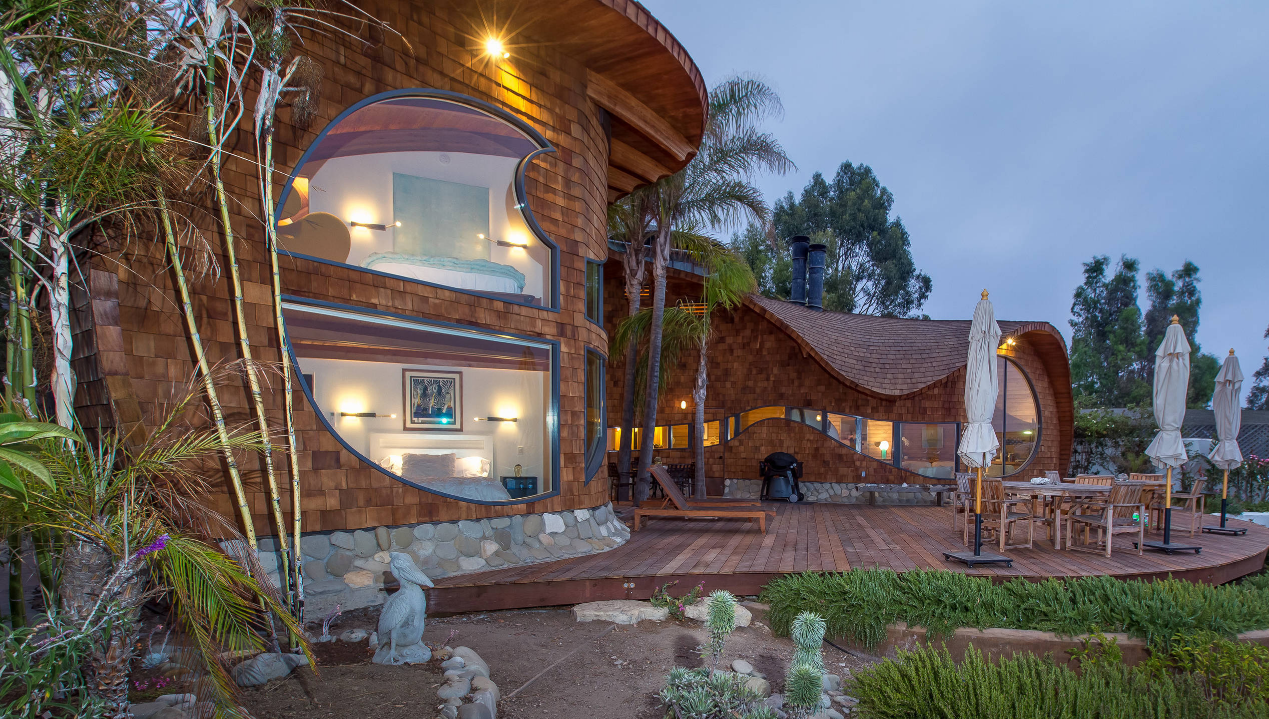 Casa à beira-mar tem formato ondulado e decoração descontraída