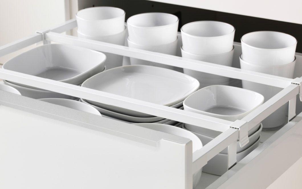 Close-up of open IKEA kitchen drawer White tableware arranged with - küchen kaufen ikea