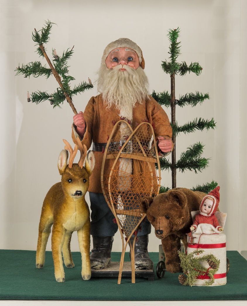 Antique Clockwork Santa with feather trees, miniature snowshoes,cotton girl candy container,and Steiff deer and bear toys.