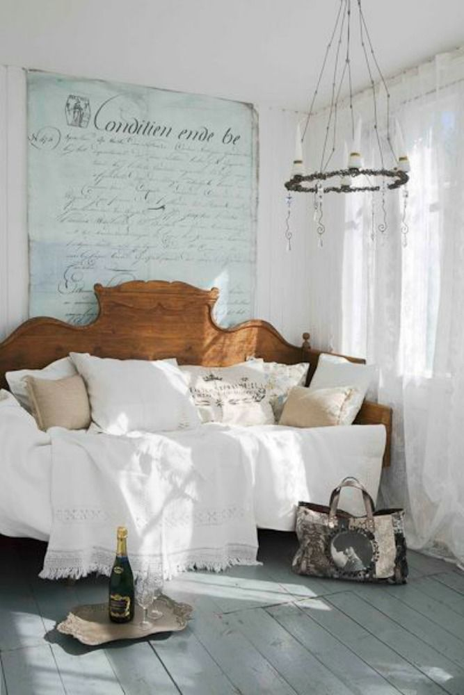 Bedroom with vintage day bed and chandelier and wall painted document.