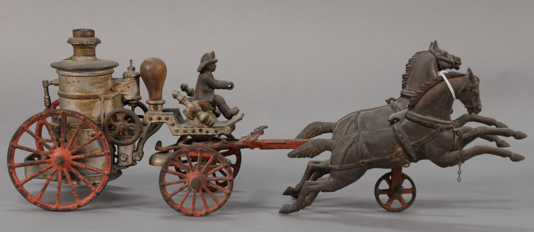 Cast iron horse drawn fire apparatus pulled by two horses, boiler door signed Phoenix, probably original silver and red paint.  ht. 7 1/4 in.; lg. 19 1/2 in.  Estimate: $250 - $450