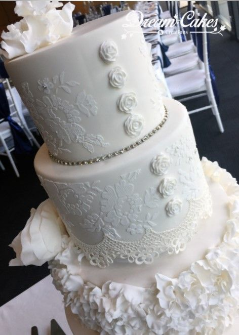 all white wedding cake edible sugar flowers and lace with ruffles showing the back of