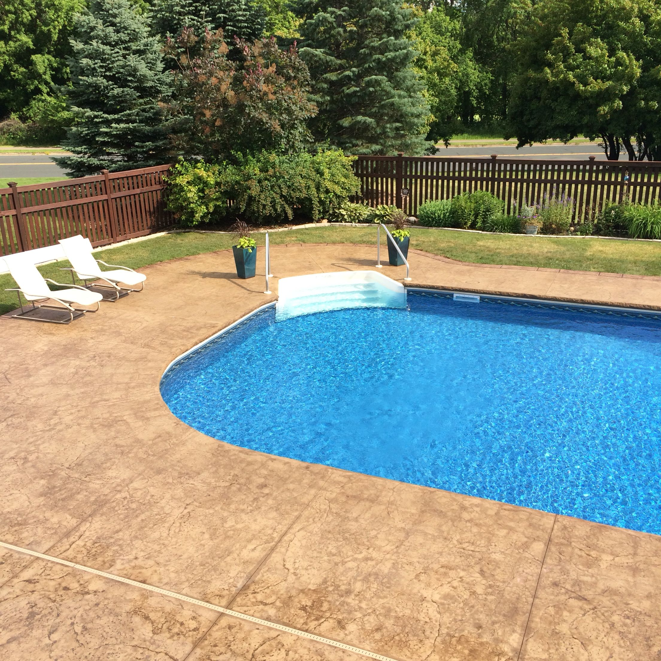 Stamped and colored concrete pool deck with custom for Concrete pool