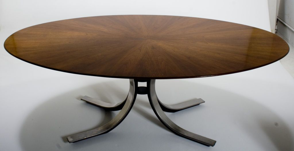 Designed by Osvaldo Borsani for Stow Davis, this oval table combines imposing dimensions and robust materials elegantly contrasted with exquisite curves and stunning walnut veneer starburst top. Polished chrome and painted iron base. USA circa 1960s - it is in excellent condition height: 28 in. depth: 47 in. width/length: 6 ft. 6 in.