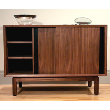 Walnut Credenza by Volk Furniture - The austerity of form showcases the richness of the wood grain that dresses this credenza, a look and feel that is almost Japanese in its ardent simplicity. Volk hand-selected the solid walnut wood and used walnut veneer on the sliding doors along with inset wenge door pulls.
