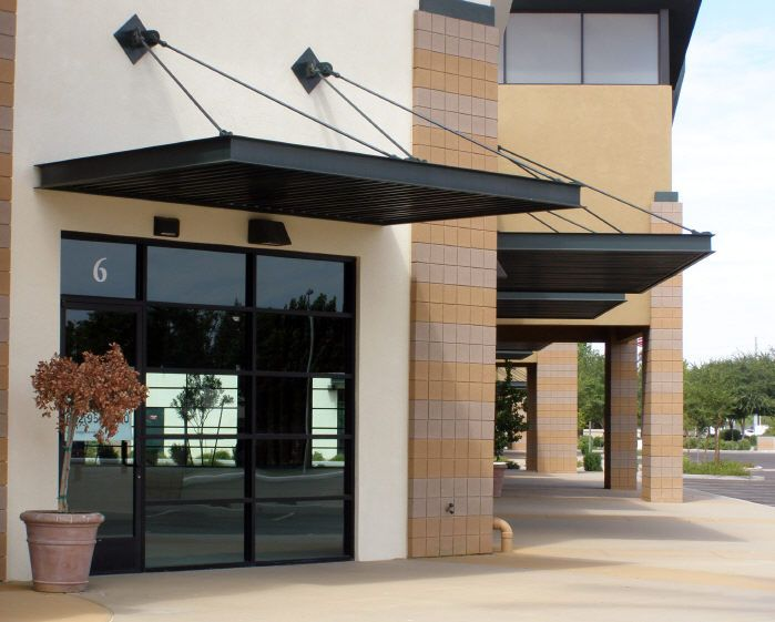 Overhead supports on commercial awnings cool retail for Modern building canopy design
