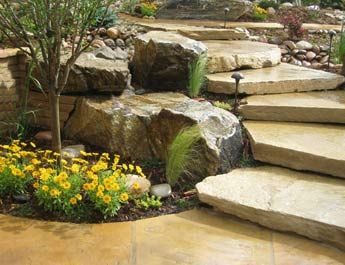 Over 2,500 square feet of sod was taken out in this beautiful custom landscape in Arvada. In its place we installed several flagstone patios, walkways, boulders and slab stairs. Xeric plantings are densely planted around all the hardscape and living spaces.