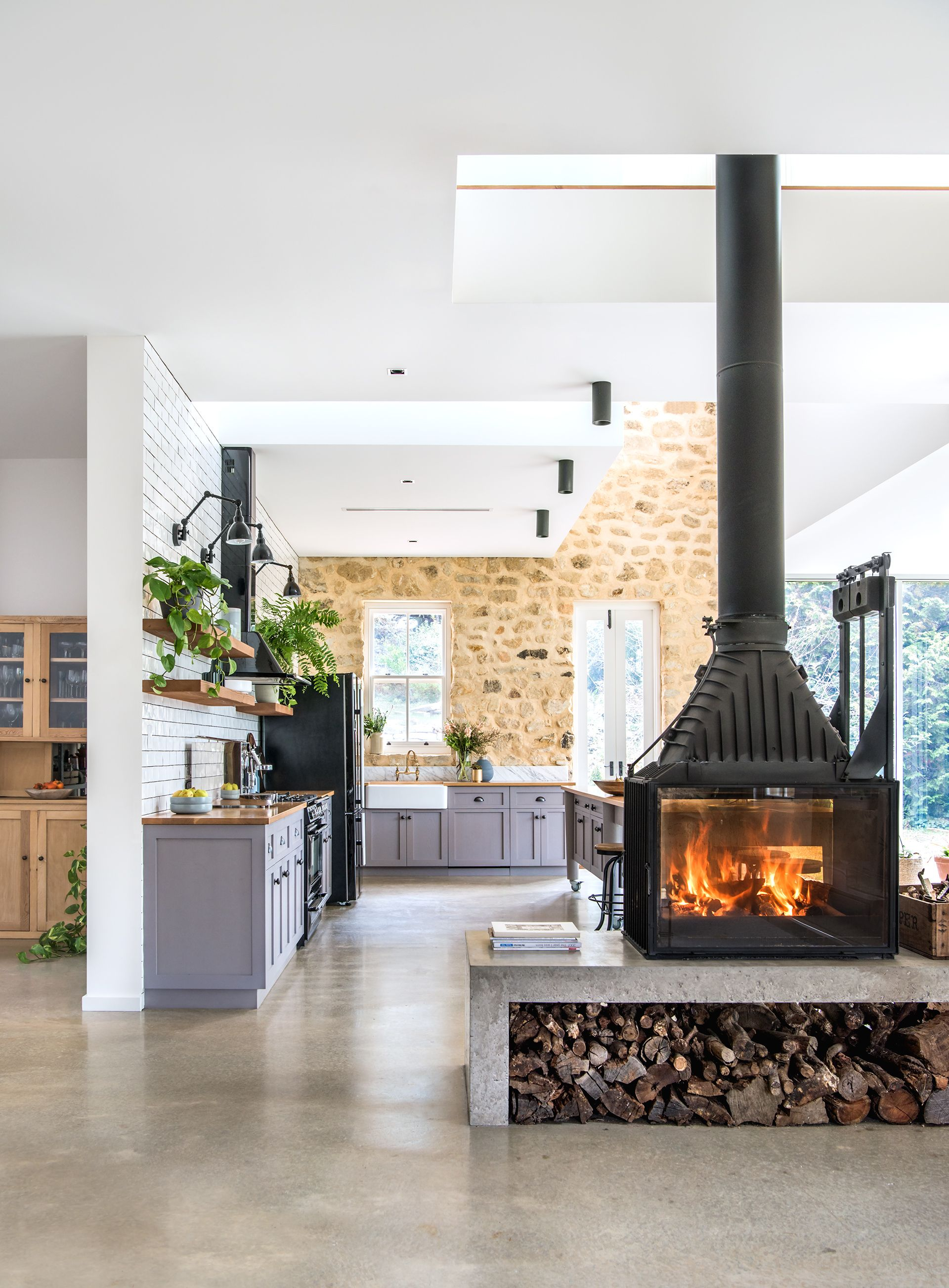 a double sided fireplace warms the living and kitchen areas in