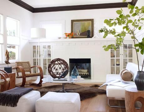 living rooms - modern craftsman home brown faux fur rug white gray marble top coffee table white leather sofa white leather square ottomans charcoal gray cashmere throw blanket white fireplace built-ins cabinets wood rocking chairs rustic wood accent tables blue vase floor lamp