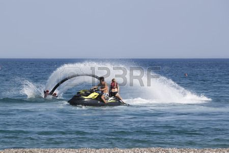 CAMYUVA, KEMER, TURKEY - JULY 16, 2015: Unidentified Turkish man demonstrates flyboard acrobatics on the beach of Camyuva. Extreme water sports are increasingly popular on the beaches of Turkey