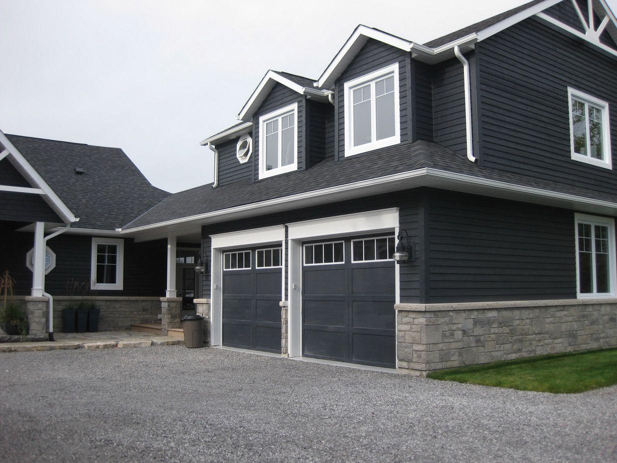 Dark bluegrey vinyl siding on a house with stone veneer
