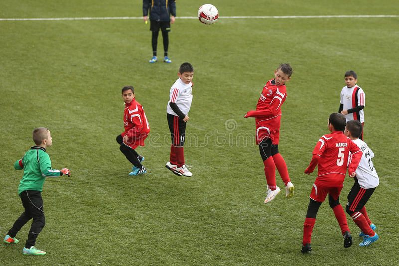 Kids playing soccer or football. Little boys pictured in