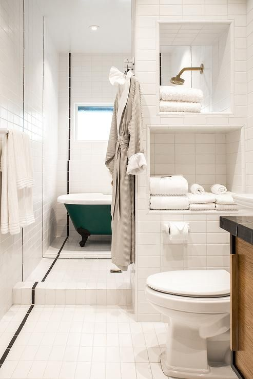 Beautiful Bathroom Features Stacked Tiled Niches Filled With Towels At The  Entrance To A Bathing Space Boasting A Green Claw Foot Tub Placed Under A  Window ...