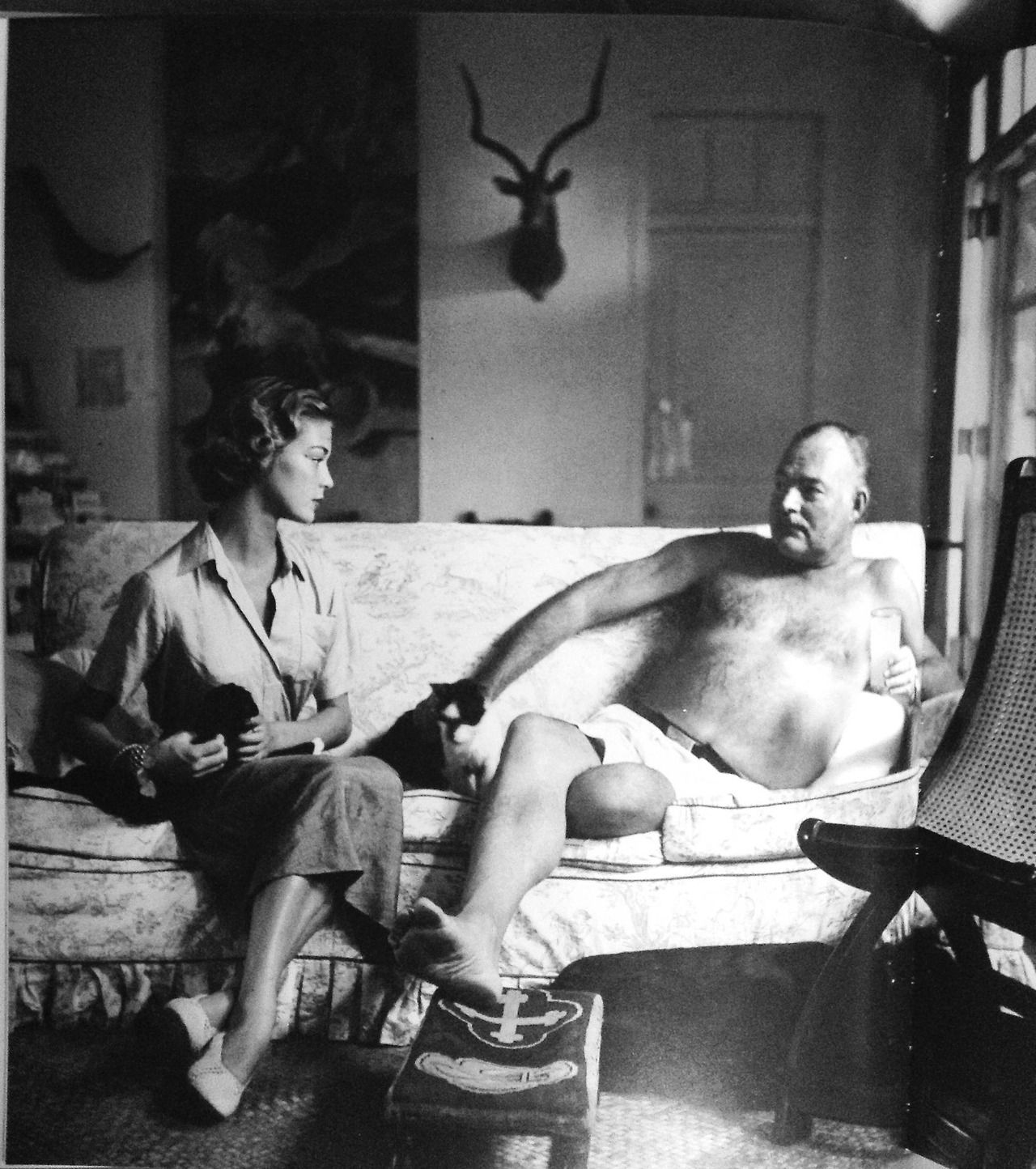 Ernest Hemingway and model Jean Patchett, sitting on a sofa in Hemingway's farmhouse in Cuba. Photo taken by Clifford Coffin