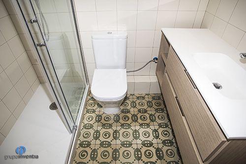El cuarto de baño dispone de lavabo con cajonera, inodoro y ducha con mamparas. Excelente combinación entre azulejos blancos y #pavimento hidráulico. #bathroom #sanitarios #bcn