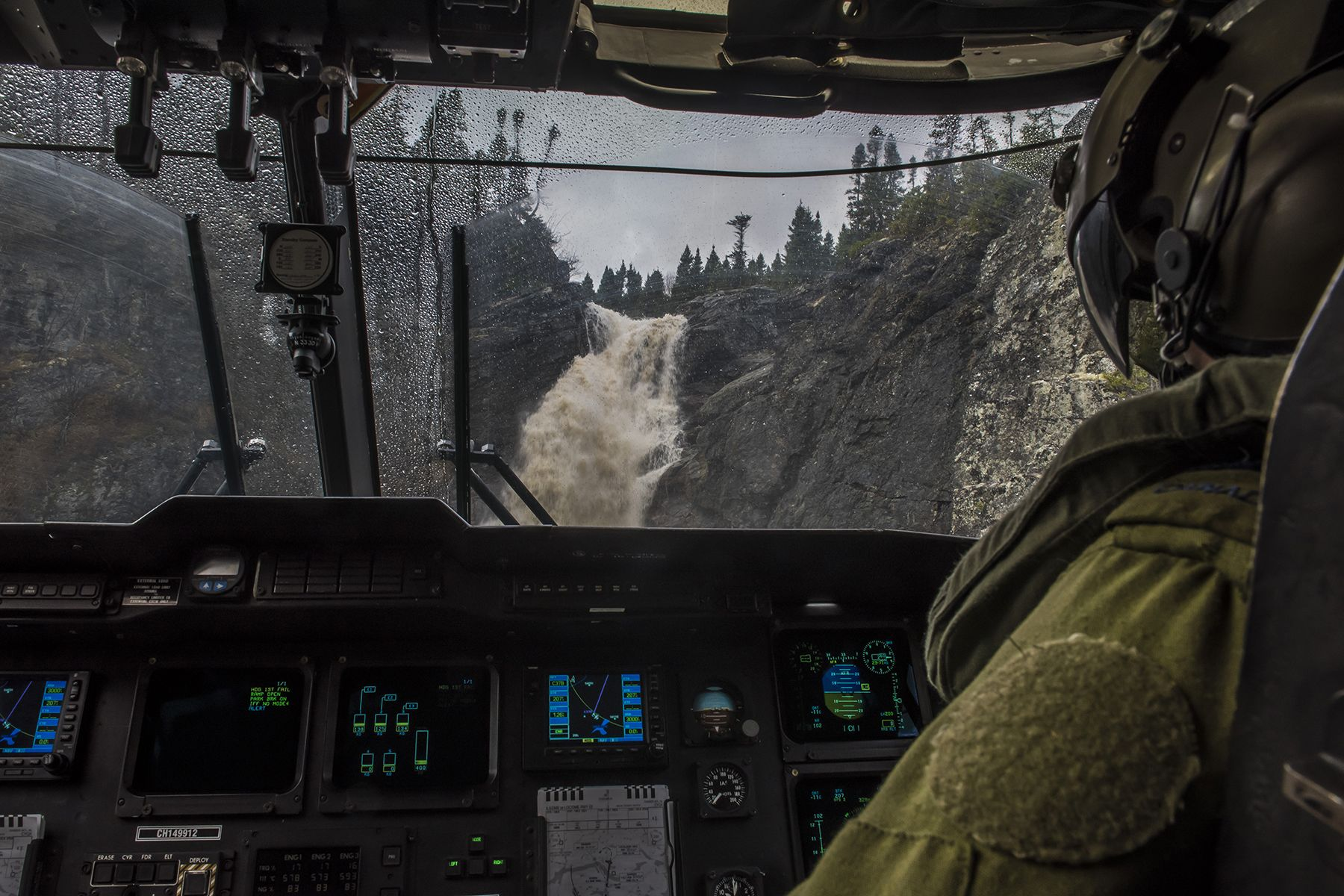 A Newfoundland waterfall's movement offers a 9 Wing Gander CH-149 Cormorant helicopter crew from 103 Search and Rescue Squadron a challenging optical illusion as they manoeuvre in a tightly confined area to land on the rocky shore below. PHOTO: Corporal Anthony Laviolette, SW2016-0099-26