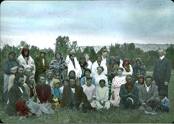 "Early 1900's Crow and non-Indian people gathered in front of bushes in Montana.  Hand written on edge of slide, ""Outside church service- Petzoldts, Misses Oden, Sims, Steer & Wafflard - teachers & matrons. Flat Head Womans, Left Hands, Yellow Tails, Bear Cranes."":"