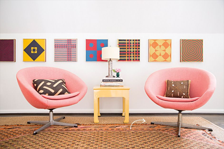 Adhering to classical principles of symmetry and scale, Benedict crafted a serene upstairs work area. The yellow lacquered side table, flanked by two pink womb-like chairs, sits in front of a series of geometric studies by artist Tom Herbert.