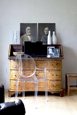 """Keskiössä: antiikkilipasto, rentouttaja:taulujen """"ripustus"""", moderni tuoli, läpinäkyvyys ei vie huomiota antiikkiesineeltä."""