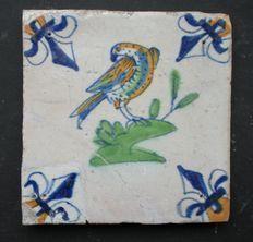 Antieke polychrome Goudse tegel met roofvogel - hoekmotief lelie