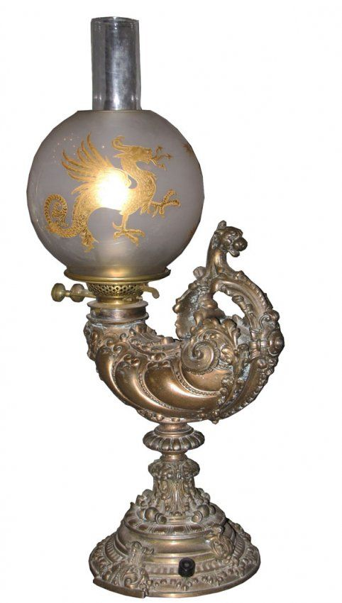 Marvelous bronze oil lamp with griffin and cherub head, acanthus leaf detailing and an absolutely stunning gold painted griffin shade. The lamp has been electrified and it has a push button switch.