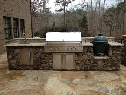 An Outdoor Stone Kitchen Island With Sink Gas Grill And Green Egg