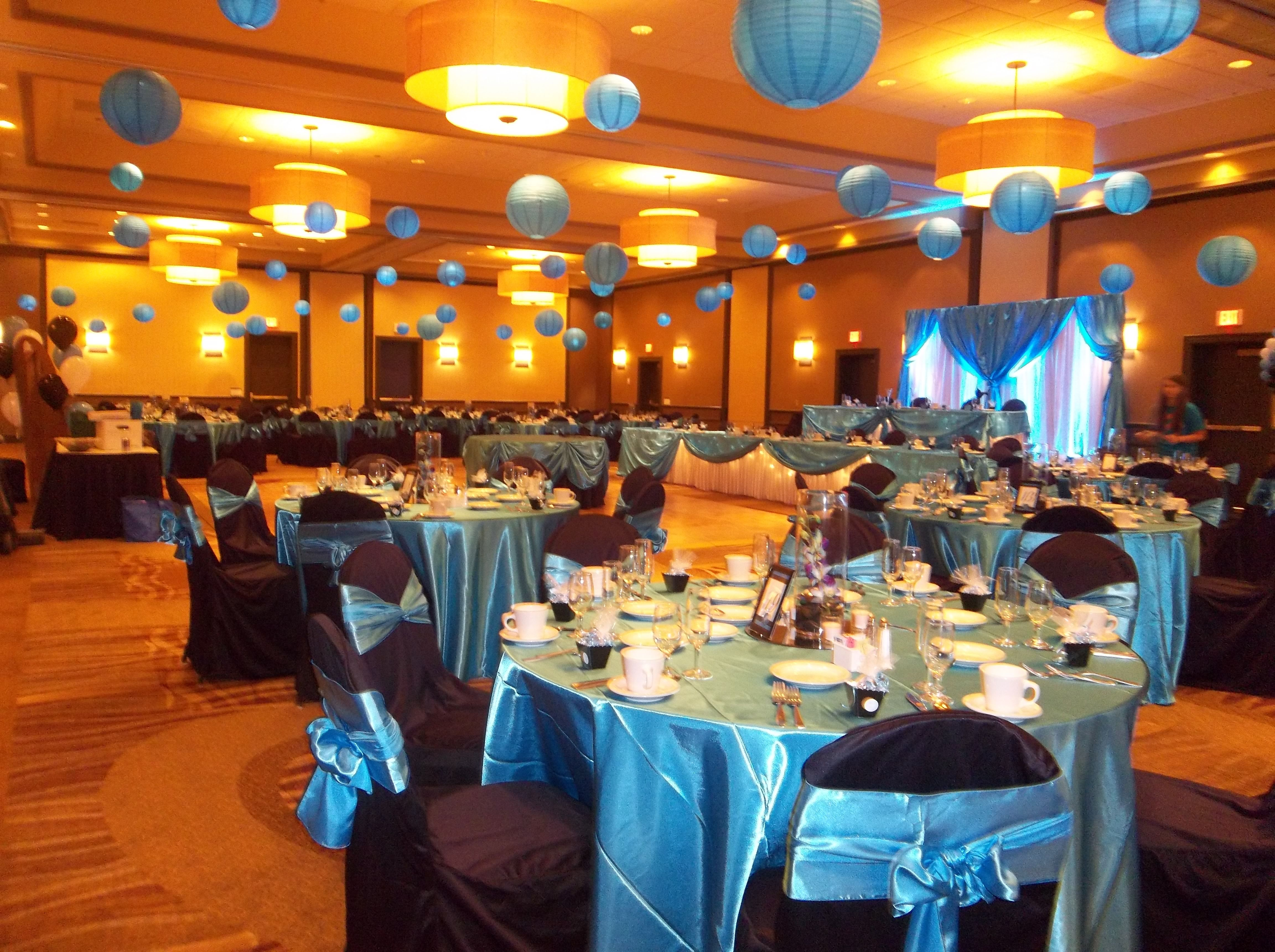 malibu blue wedding with black chair covers and lighted lanterns