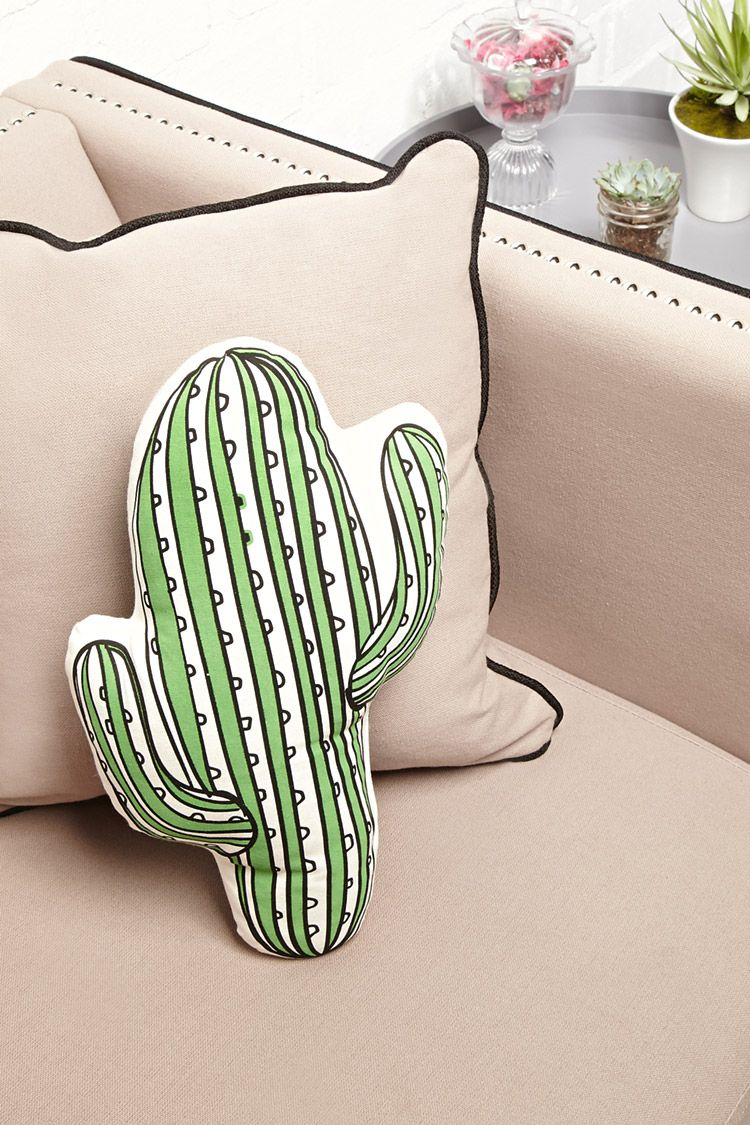 A canvas pillow with a cactus cutout design and striped pattern ...