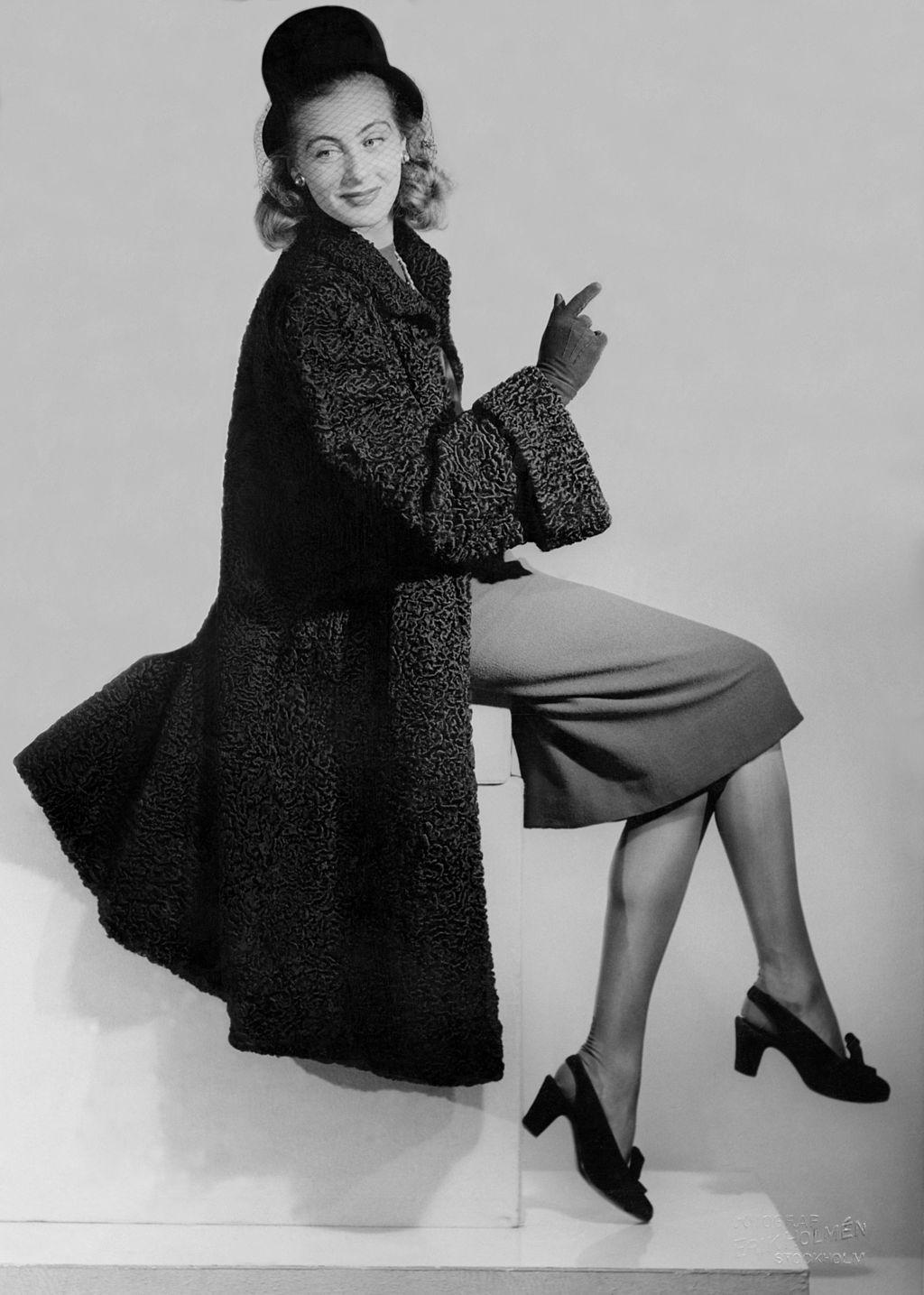 860026b0129a Nordiska Kompaniet visar pälsmode. Modell klädd i persianpäls och hatt med  flor. 1945. Foto: Erik Holmén. CC-BY.