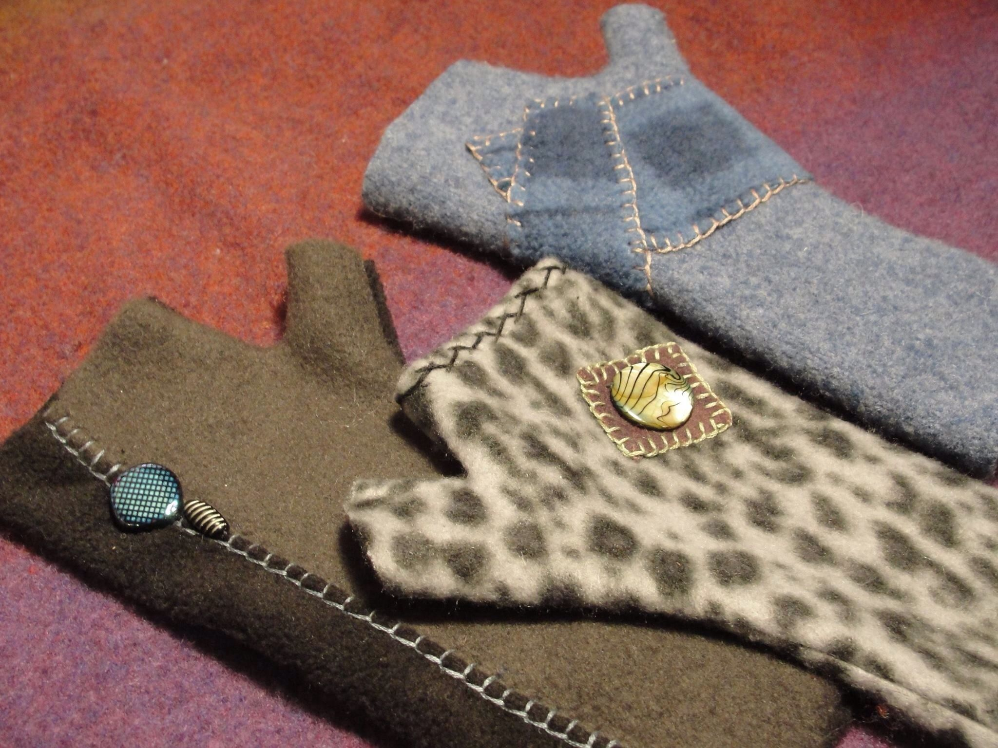 Trio of fingerless mittens with hand stitching and appliqué.  Fleece and felted wool.