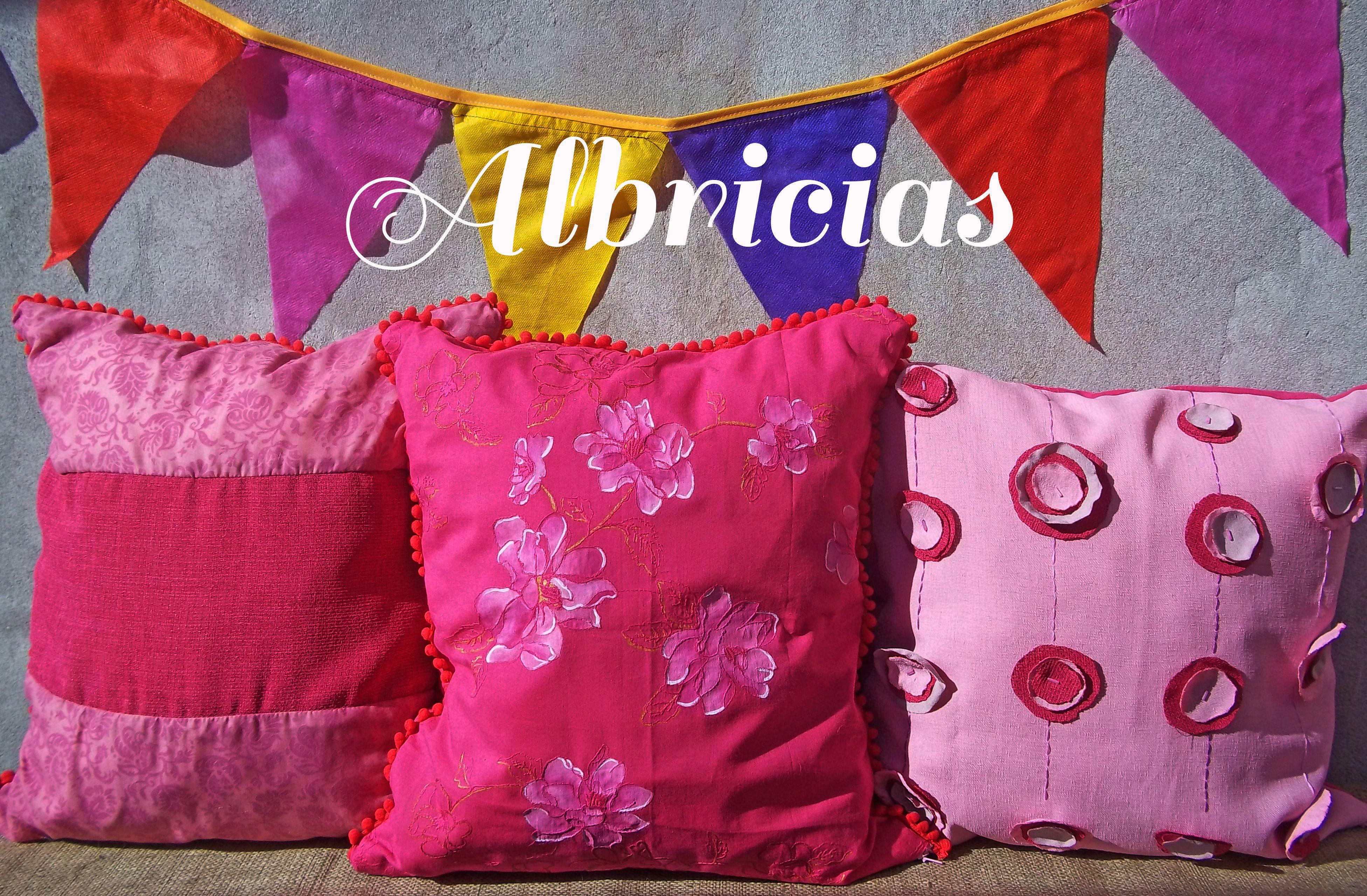 Almohadones de lino y batista bordada, con apliques de flores, pompones y pintura amano.