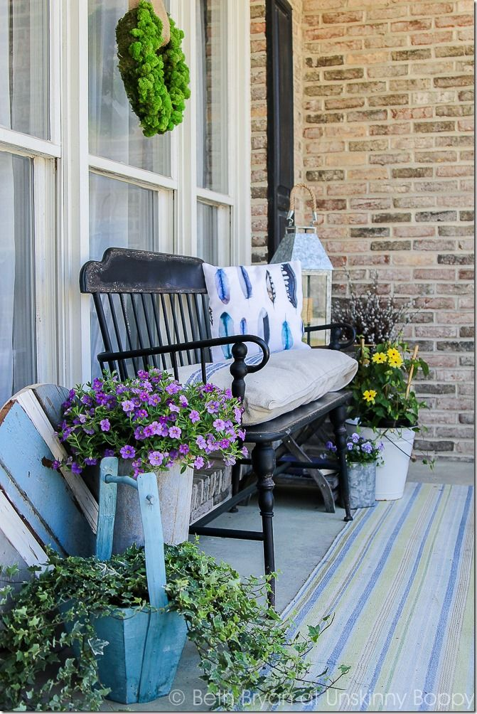 front porch seating. Black Metal Front Porch Bench With Watercolor Feather Pillow, French Grain Sack Cushion And Flowers In A Bucket For Spring | Cozy Home Tour Seating