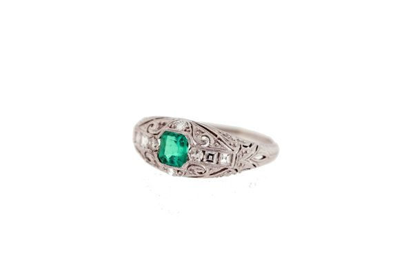 Diamond and emerald ring made in Platinum with filigree and milgrain accents. This wonderful ring measures 8.1 millimeters wide 19.44 millimeters long and is 4.2 millimeters tall. It is not able to be resized and its a size six and three quarter.    Please review policy section