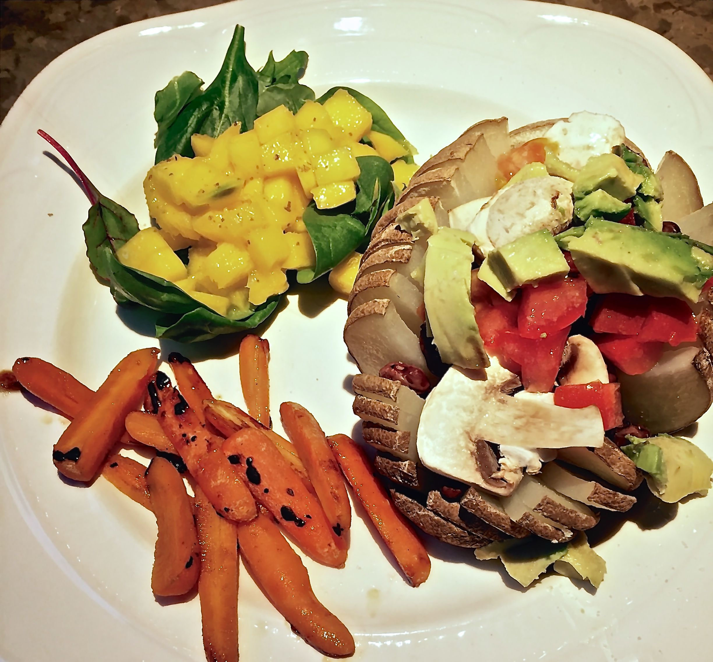 Baked potato with mushrooms, beans, avocado and tomatoes. Mango and spinach plus carrots with honey and lime.