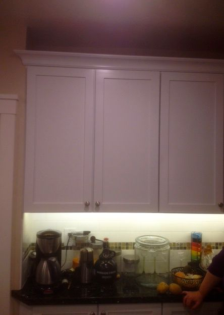 White shaker style cabinets. LED under cabinet lighting. Basic crown moulding on top of cabinets.
